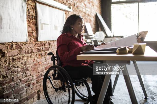 businesswoman in wheelchair working at desk - small business stock pictures, royalty-free photos & images