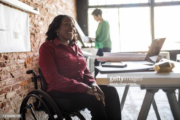 businesswoman in wheelchair working at desk - disabilitycollection stock pictures, royalty-free photos & images
