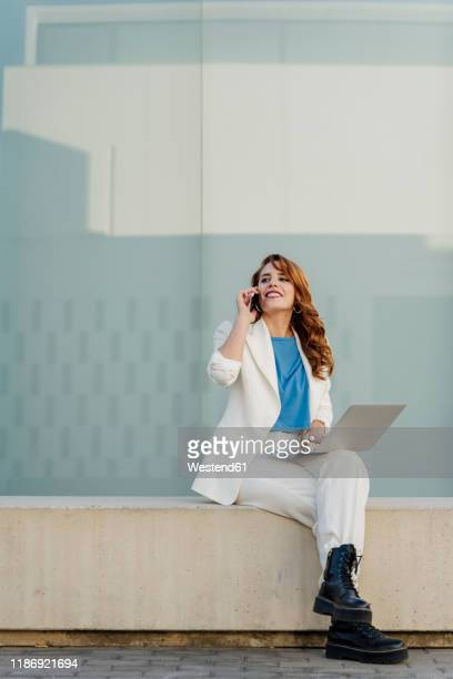 businesswoman in white pant suit, sitting on bench, using laptop, talking on the phone - vestuário de trabalho imagens e fotografias de stock