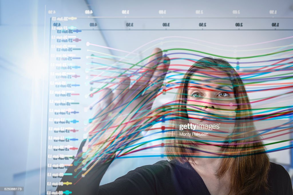 Businesswoman inspecting graph on interactive display : Stock Photo