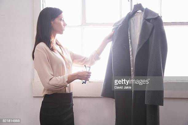 businesswoman inspecting grey coat - lapel stock pictures, royalty-free photos & images