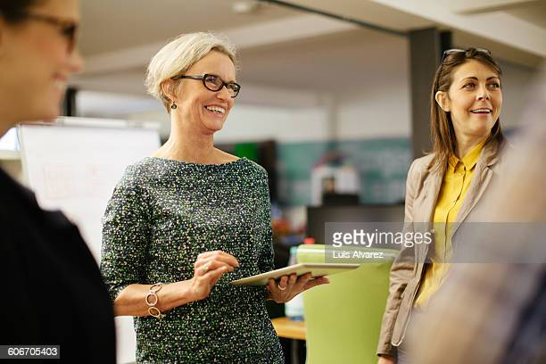 businesswoman interacting with colleagues - vanguardians stock pictures, royalty-free photos & images