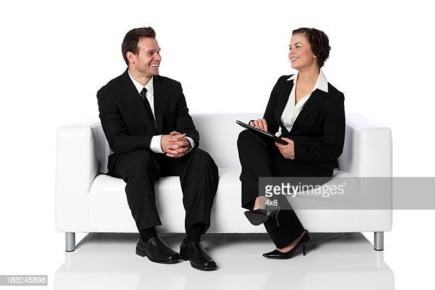 Businesswoman interviewing man on a couch