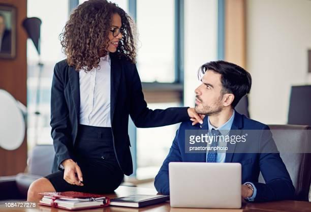 zakenvrouw is flirten met haar collega in het bureau - kantoorromance stockfoto's en -beelden