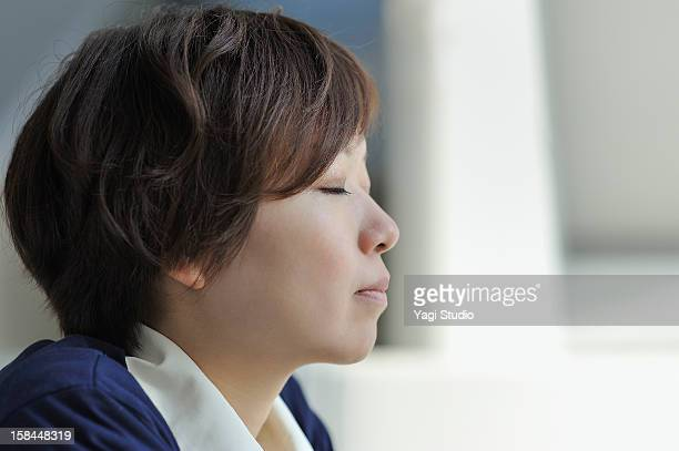 Businesswoman is relaxing with closed eyes