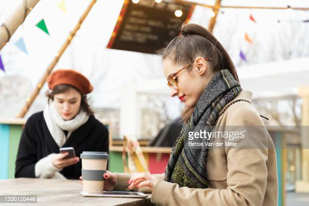 businesswoman is working on digital device, sitting in outdoor cafe. - on the move stock pictures, royalty-free photos & images