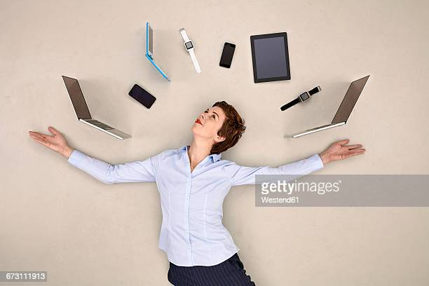 businesswoman juggling mobile devices - surrounding stock pictures, royalty-free photos & images