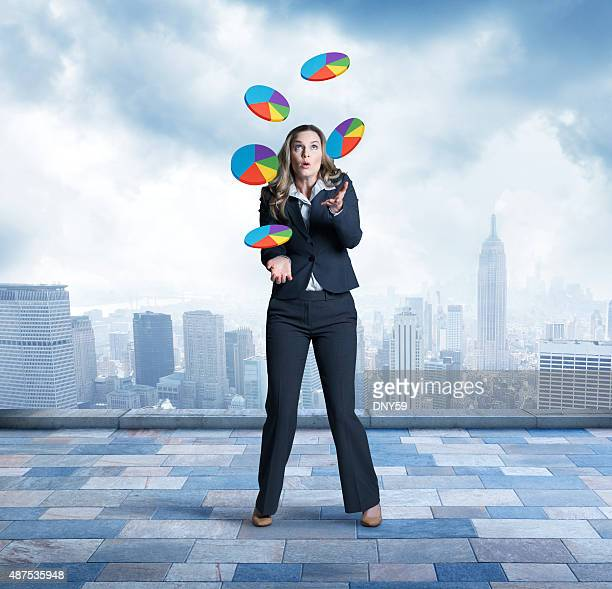 Businesswoman juggling pie charts in front of city skyline