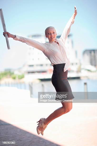 Businesswoman jumping for joy