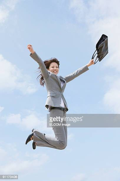 Businesswoman jumping, holding bag