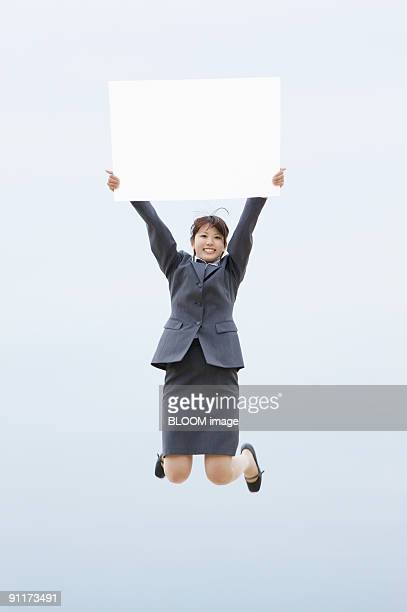 Businesswoman jumping, holding whiteboard