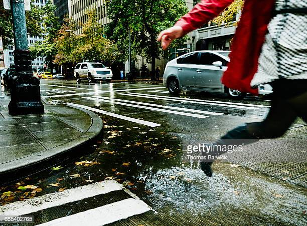 Businesswoman jumping over puddle on city street