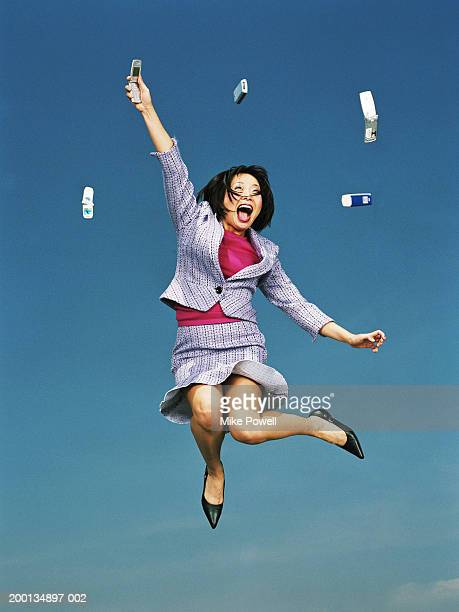 Businesswoman jumping with mobile phones in air, low angle