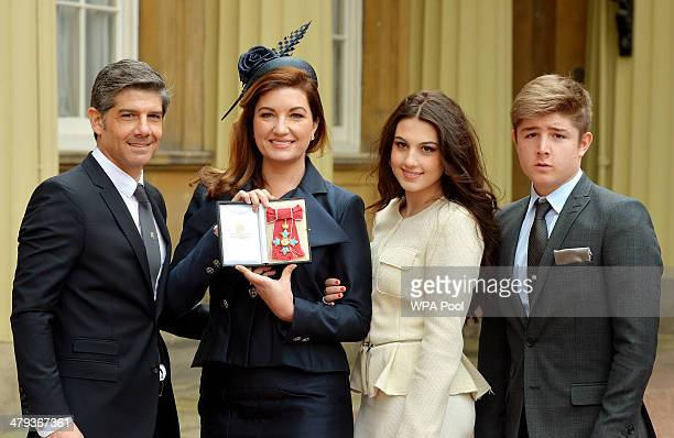 Businesswoman Karren Brady holds her CBE as she poses with her husband Paul Peschisolido and children Sophia and Paolo presented to her by the Duke...