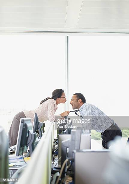 Businesswoman kissing co-worker in office