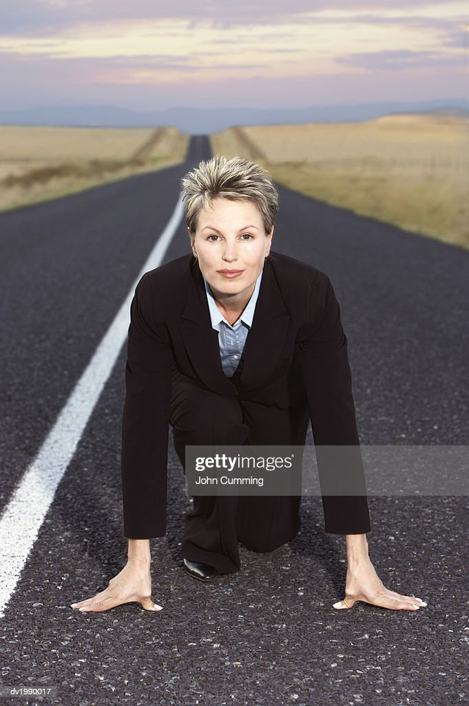 Businesswoman Kneeling on a Remote Road in Preparation for a Race : Stock Photo