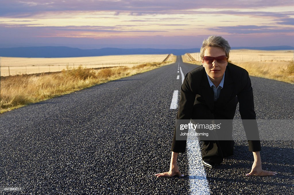 Businesswoman Kneeling on Starting Blocks on a Country Road : Stock Photo