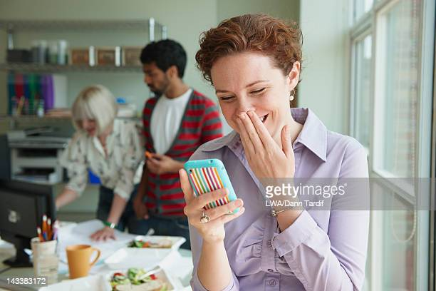 Businesswoman laughing at text message