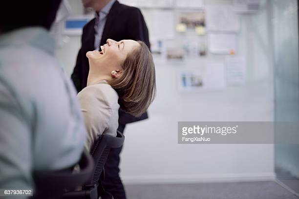 businesswoman laughing reaction in office team meeting - rindo - fotografias e filmes do acervo