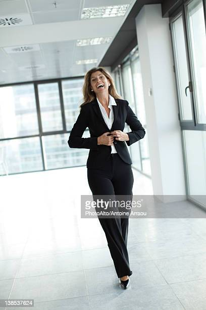 Businesswoman laughing while walk toward camera