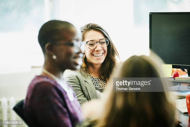 businesswoman laughing with coworkers at workstation in office - desktop pc stock pictures, royalty-free photos & images