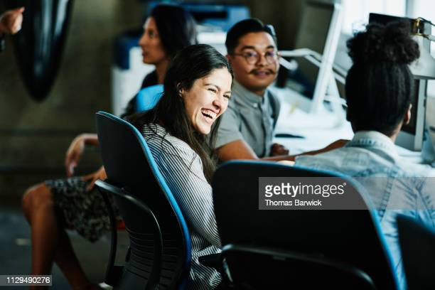 businesswoman laughing with coworkers while working in design studio - adulte d'âge moyen photos et images de collection