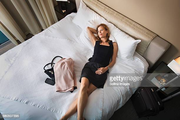 Businesswoman laying on hotel bed