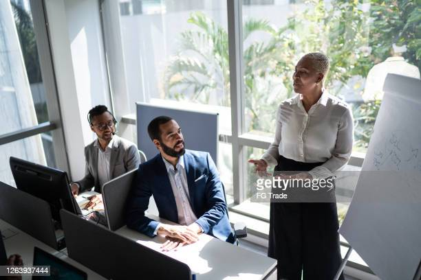 businesswoman leader speaking with her team giving a flipchart presentation - founder stock pictures, royalty-free photos & images