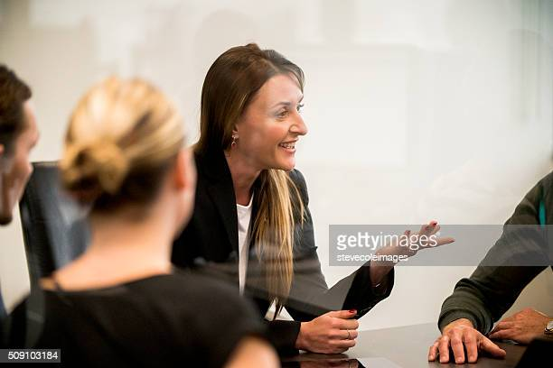 businesswoman leading a meeting. - culturen stockfoto's en -beelden