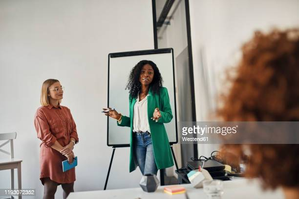 businesswoman leading a presentation at flip chart in conference room - pbs stock pictures, royalty-free photos & images