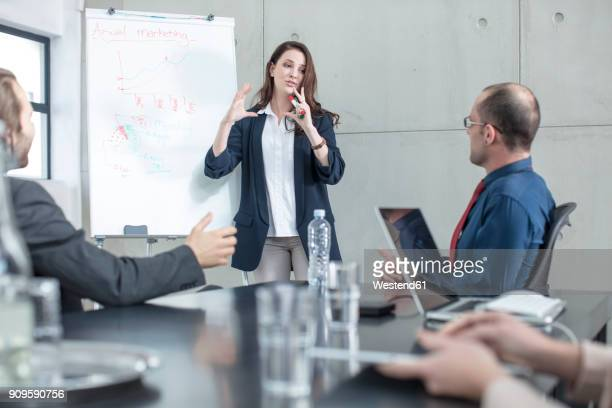 businesswoman leading a presentation on a meeting in conference room - pbs stock pictures, royalty-free photos & images