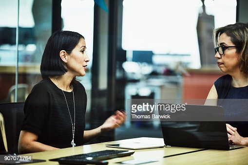 Businesswoman leading client meeting in office conference room