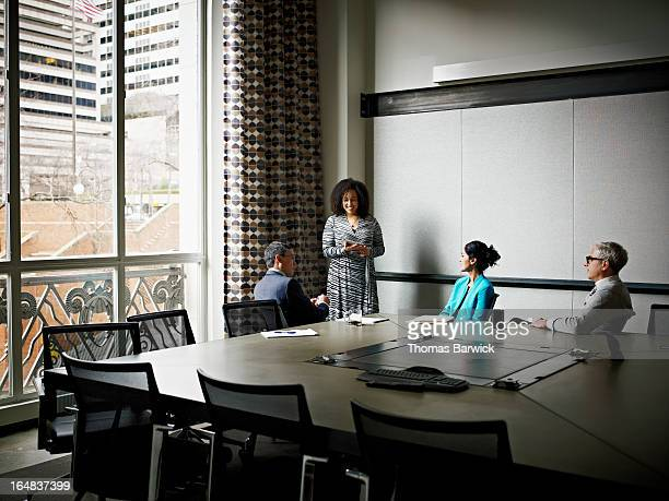 businesswoman leading discussion in office - leanintogether stock pictures, royalty-free photos & images