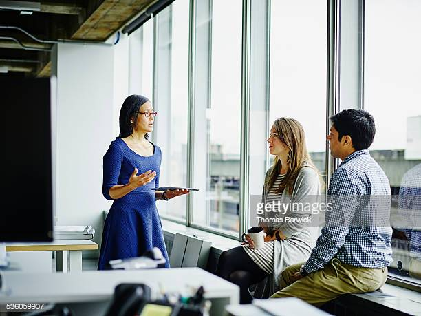 businesswoman leading discussion with colleagues - leanincollection stock pictures, royalty-free photos & images