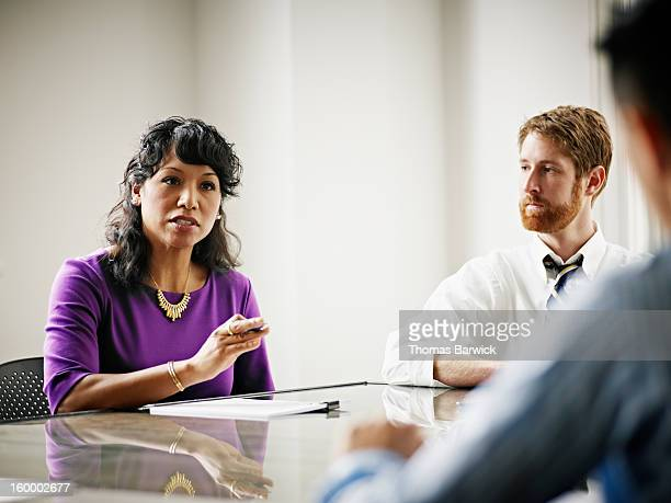 businesswoman leading discussion with coworkers - leanincollection stock pictures, royalty-free photos & images