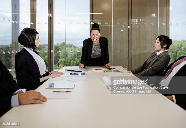 businesswoman leading discussion with coworkers - aggression stock pictures, royalty-free photos & images