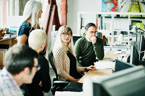 Businesswoman leading group discussion with colleagues at workstations in design office - gettyimageskorea
