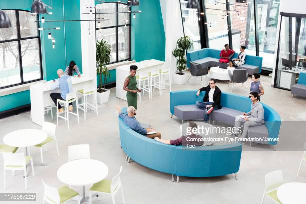 businesswoman leading informal meeting in modern open plan office - nova empresa - fotografias e filmes do acervo