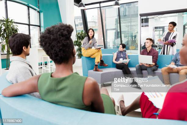 businesswoman leading informal meeting in modern open plan office - ocupação criativa imagens e fotografias de stock