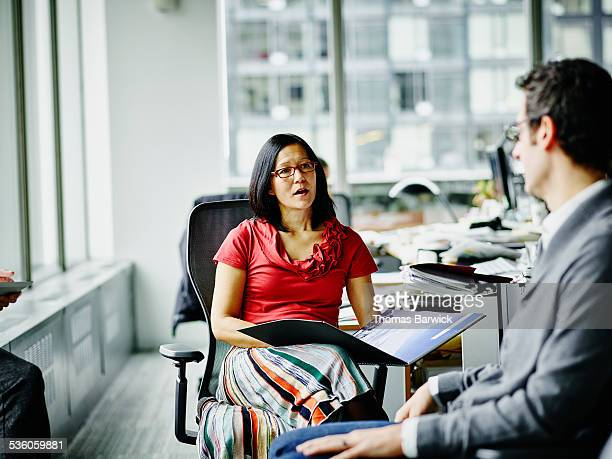 businesswoman leading informal meeting in office - leanintogether stock pictures, royalty-free photos & images