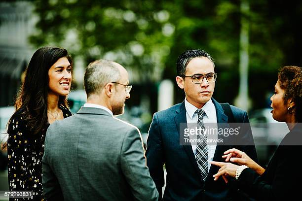 Businesswoman leading informal meeting on sidewalk