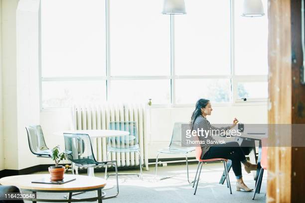 businesswoman leading meeting in start up office conference room - 足を組む ストックフォトと画像