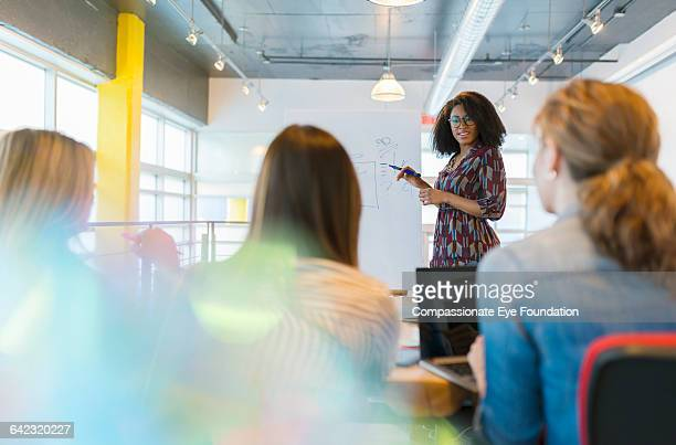 businesswoman leading meeting - businesswear stock pictures, royalty-free photos & images
