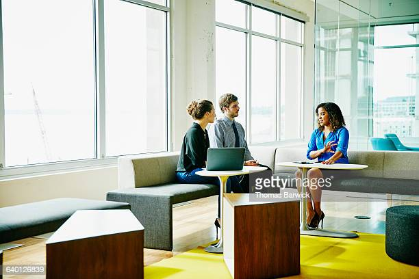 Businesswoman leading meeting with colleagues