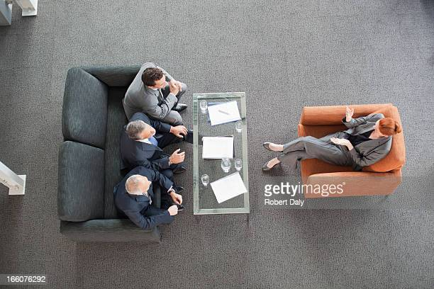businesswoman leading meeting with co-workers in lobby - persuasion stock pictures, royalty-free photos & images