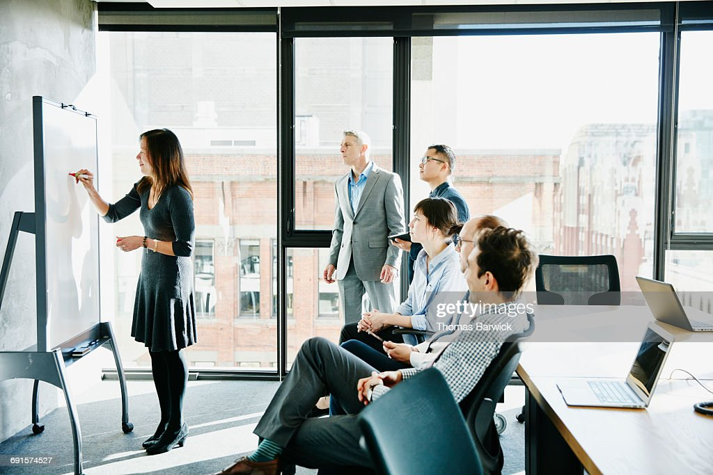 Businesswoman leading presentation at whiteboard : Stock Photo