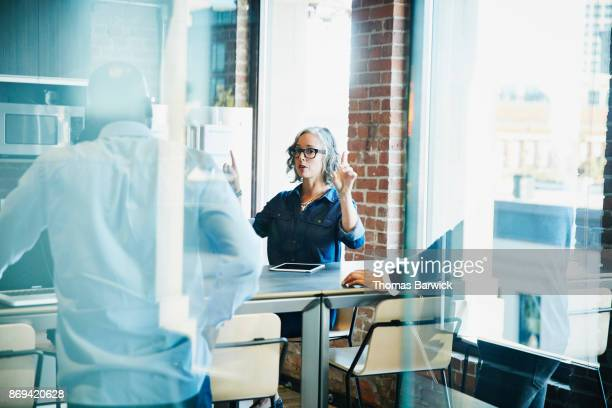 Businesswoman leading project discussion during informal meeting in office kitchen