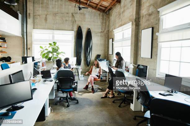 businesswoman leading project meeting with colleagues in design office - デザインスタジオ ストックフォトと画像