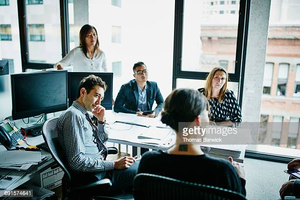 businesswoman leading team meeting at workstation - formal businesswear stock pictures, royalty-free photos & images