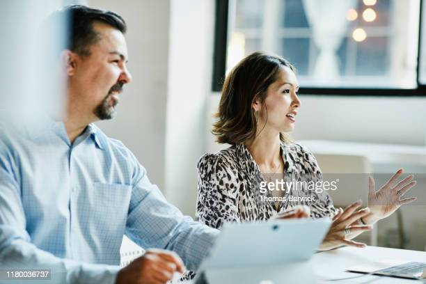 businesswoman leading team meeting in coworking office - business meeting stock pictures, royalty-free photos & images